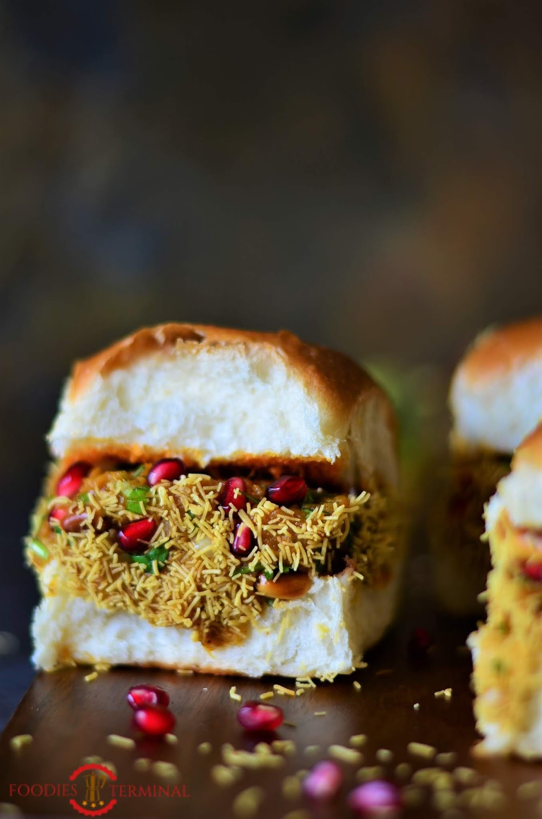 Kacchi Dabeli all ready, garnished with crunchy pomegranate seeds, sev and masala peanuts. Make this tasty dabelic at home now.