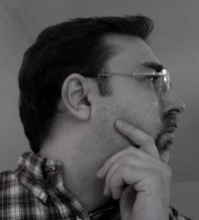 a portrait of the author in profile — male with dark hair, glasses, mustache and goatee, wearing a plaid shirt, hand resting on his chin as if in thought