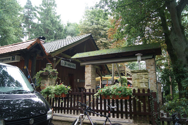 """Ein Holzhaus im Wald. Auf einem Schild steht """"Almhütte"""""""