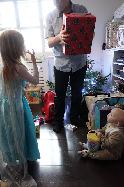 2 children looking up at a man holding a large present