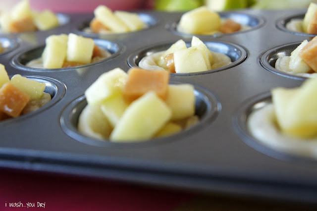 A close up of a muffin tin with chopped apples and chopped caramel candy mix added to each muffin space.