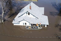 Lanni Bailey and a team from Muddy Paws Second Chance Rescue enter a flooded house to pull out several cats during the flooding of the Missouri River near Glenwood, Iowa, on March 18, 2019. (Credit: Passport Aerial Photography/Handout via Reuters