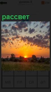 Над полем с ограждением поднимается солнце на рассвете, освещая простор природы