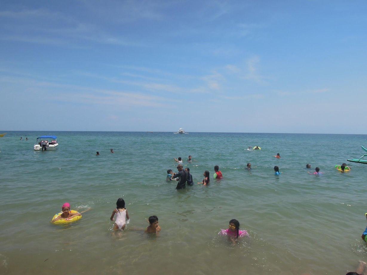 Swimmers enjoying the beach at Paseo Verde Beach Resort