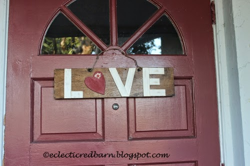 Eclectic Red Barn:  LOVE sign hanging at door with barbed wire hanger