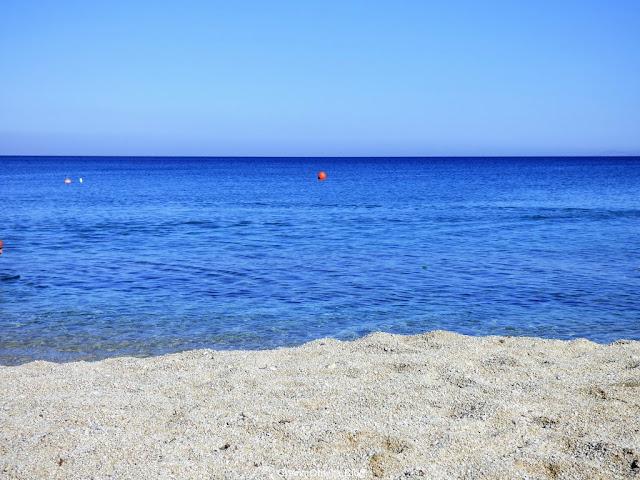 Bezchmurene greckie niebo, błękitne cykladzkie morze, czysta plaża Mykonos.