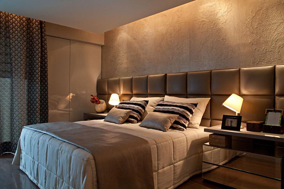 2e21f04c1 Cama com cabeceira de placas estofadas e revestidas de couro ecológico.  Detalhe para a parede da cabeceira revestida com painel em alto relevo e  iluminação ...