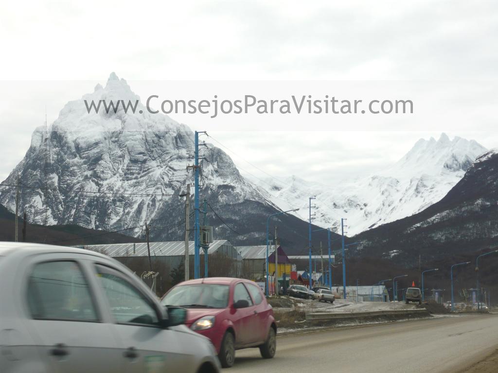 autos viajando hacia las altas montañas con nieve en Ushuaia