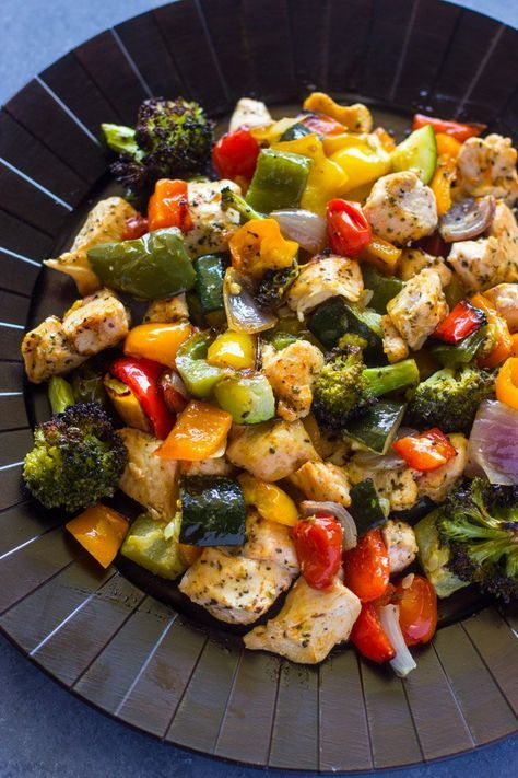 Healthy chicken breast pieces and vegetables coated with Italian seasoning, olive oil and baked (roasted) in the oven for 15 minutes.