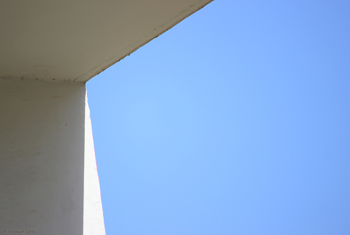 A minimalist photo of the Corner of a white wall against the blue sky