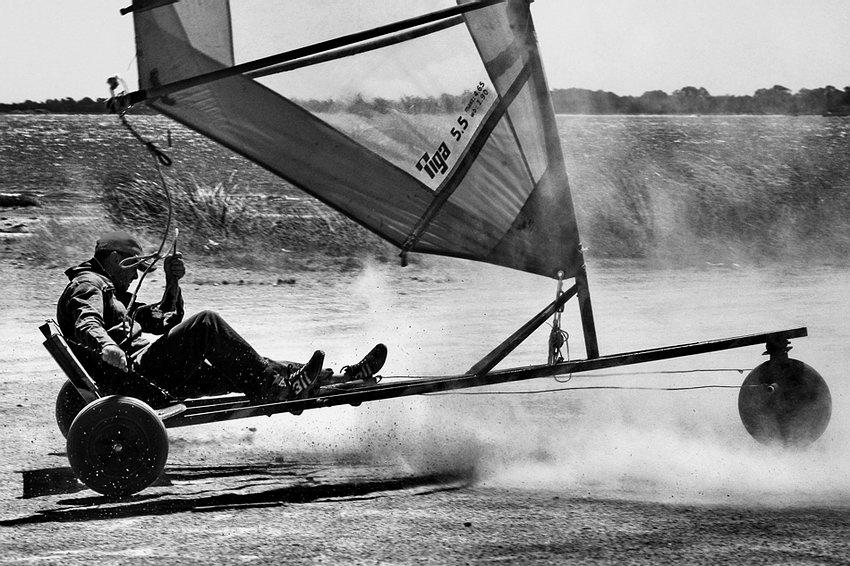 Foto de acção a preto e branco, apresentando o triciclo e o seu piloto a manobrar com bastante velocidade