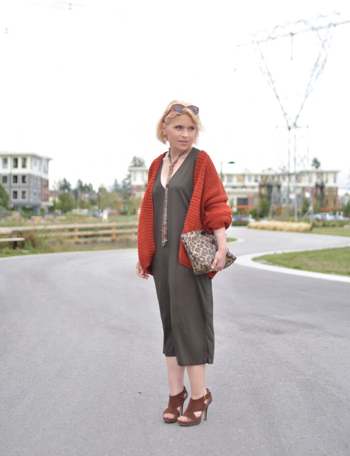 Monika Faulkner styles an olive jersey caftan with a chunky-knit cardigan, suede heels, and leopard-print clutch