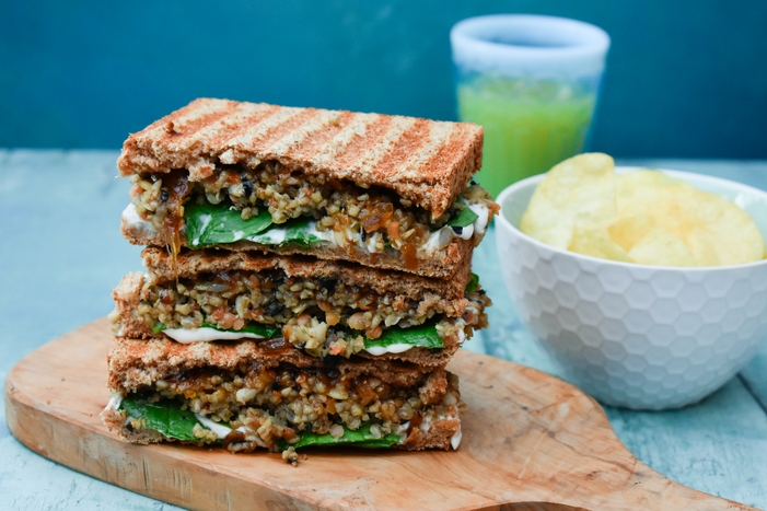 Veggie Haggis and Onion Chutney Toastie cut in half and stacked on a wooden board