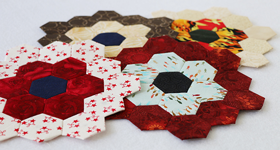 Angled View of Four Hand Sewn English Paper Piecing Hexagon Flowers