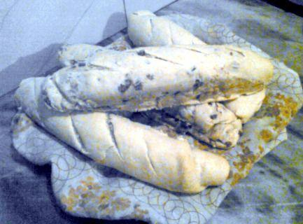 Pan de queso y chicharrones. Cuatro panes horneados sobre un mantel, dos de ellos con chicharrones.