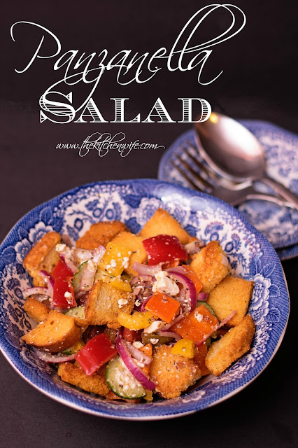 The finished panzanella salad in a blue china bowl and the title at the top.