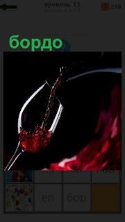 В рюмку наливают красное вино под названием бордо из Франции