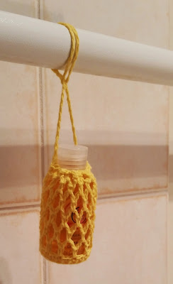 A white bathroom rail runs horizontally across the top of the photograph. Hanging from it is a shower gel bottle encaed in its mesh bag. The drawstring has been looped over the rail and the bag to secure it to the rail.