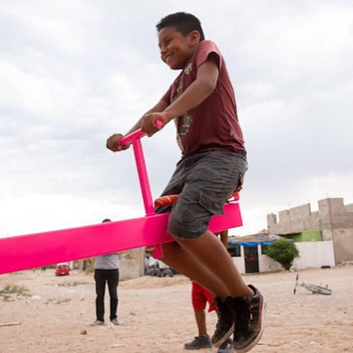 US And Mexico Kids Play Together On Seesaws Built On The Border Wall In Defiance Of Donald Trump