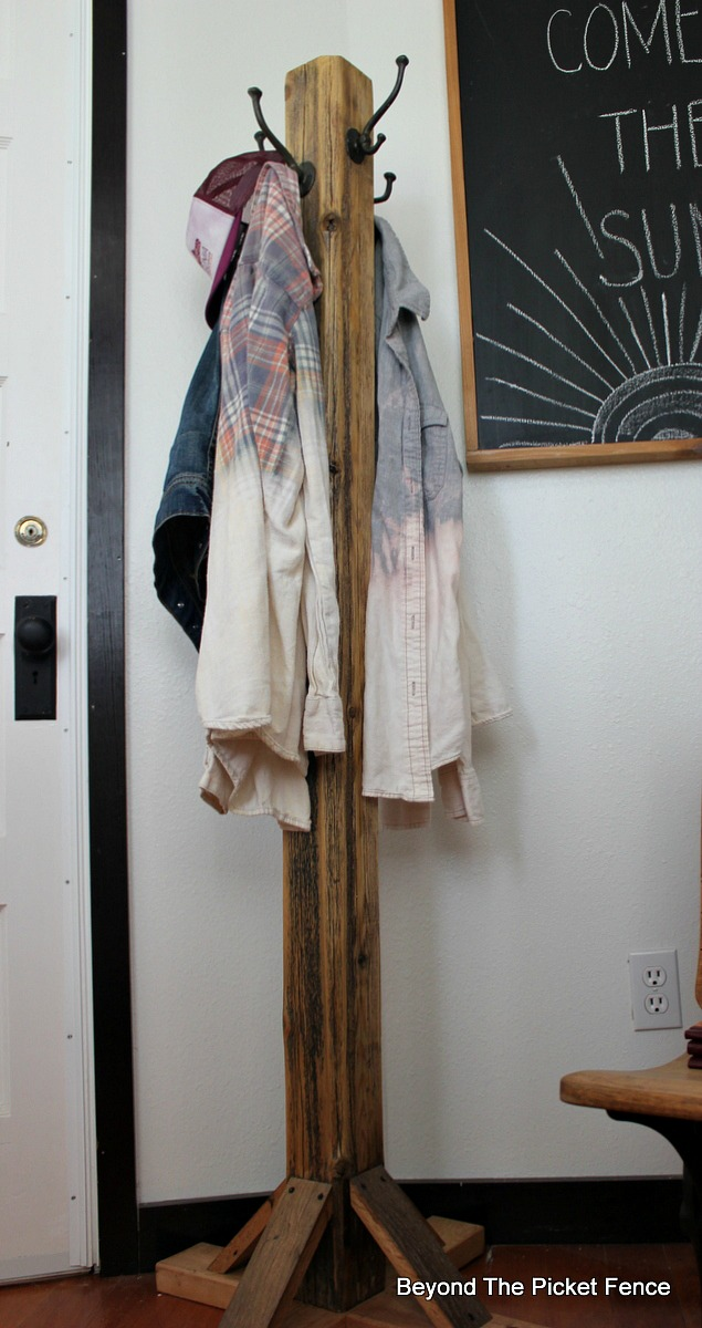 add hooks to an old fence post to make a coat tree