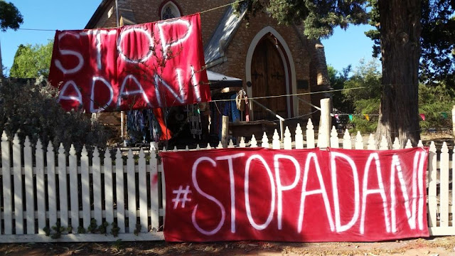 "The garden of a church is decorated with red fabric banners with the white spraypainted words ""#STOP ADANI"". One banner is tied to a white picket fence and the other is suspended between trees. The church building is in teh background."