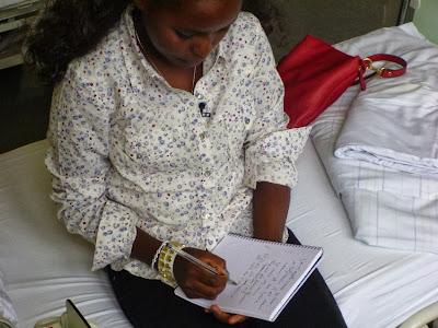 Patientin sitzt auf dem Bett und schreibt