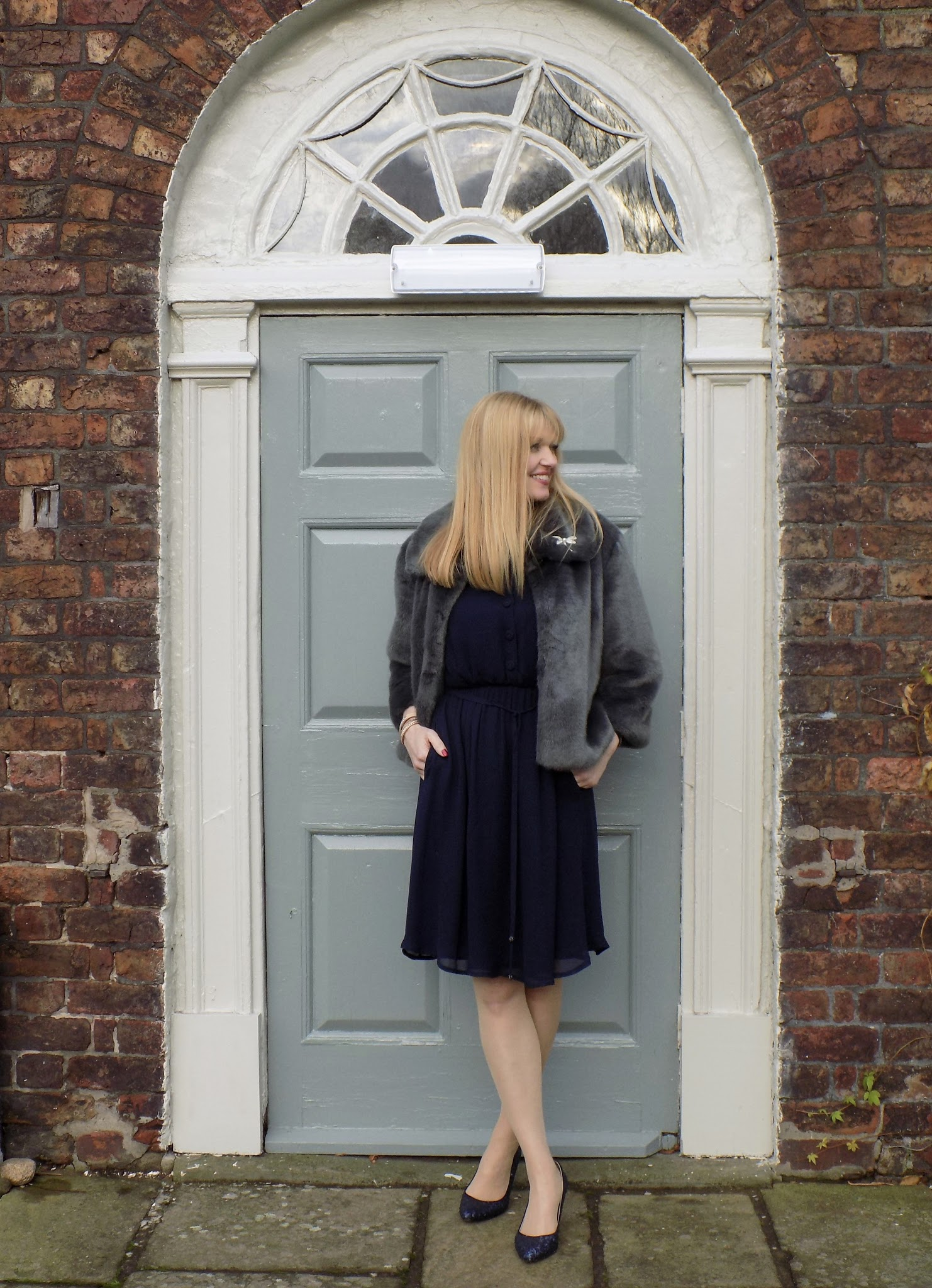 Little navy dress with navy sequinned shoes and greay faux fur jacket