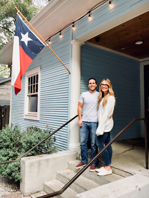 couple smiling on front porch with texas flag flying