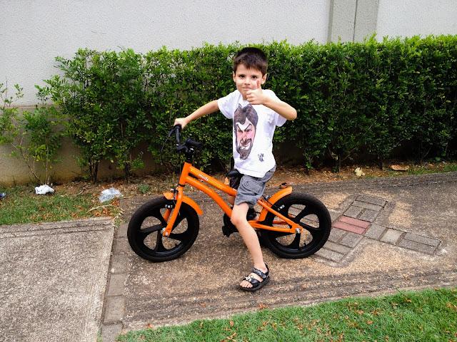 Meu filho fazendo joinha em cima de sua bicicleta.