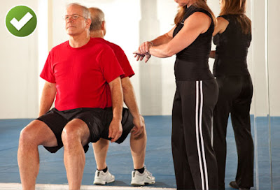 Man Doing Wall Sit With Trainer Timing