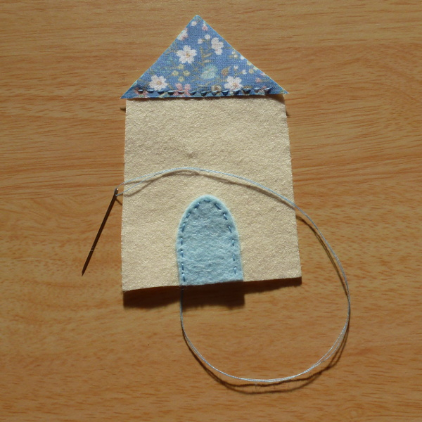 Blue fabric and felt detail being hand sewn onto a felt house