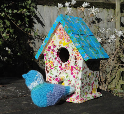 Decoupaged birdhouse with knitted bird