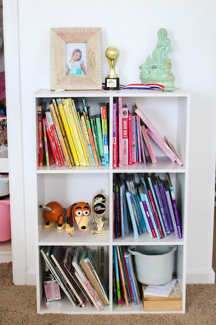 Books sorted by the rainbow in a shared girls' room