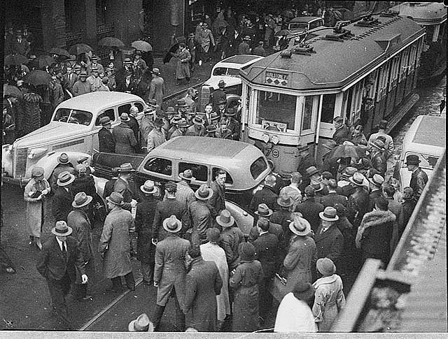 Tram and taxi smash in Pitt Street, 25/6/1937 / Sam Hood. Notes: Trams and their operation were blamed for many accidents in Sydney's narrow streets. In this case, traffic in Pitt Street was held up when a taxi pulled out from the curb and was struck by one of Sydney's notorious 'toast rack' trams. Pedestrians have added to the confusion, creating a bottleneck. In 1921 regulations were passed which required motorists to signal their intention to stop or turn, but hand signals were not always given or seen.