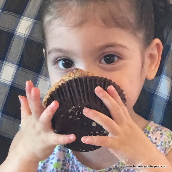 child smushes a muffin into her face at Bakery Lorraine in the Pearl in San Antonio, Texas