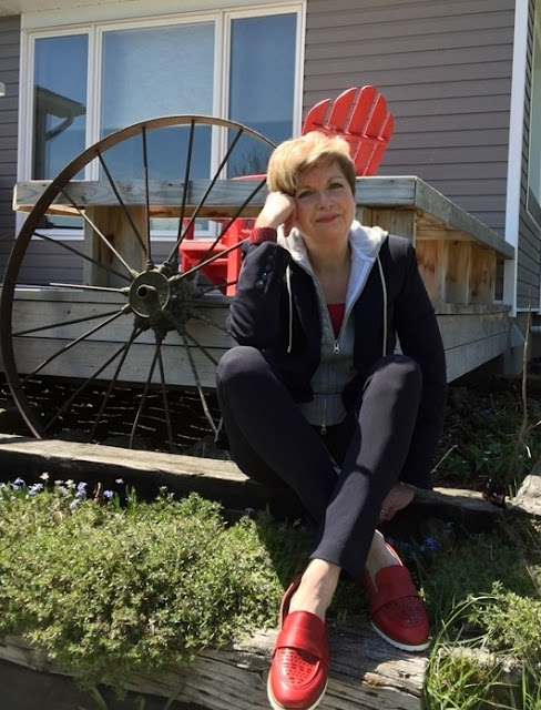 woman in navy suit and red shoes, sitting in front of a deck, old wagon wheel behind her.