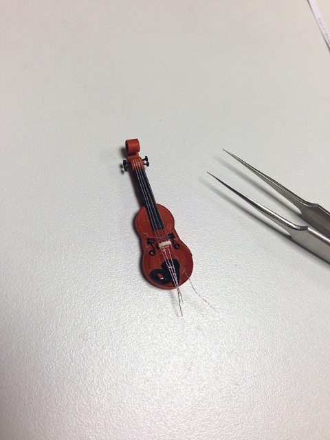 quilled violin in progress with needle-tip tweezers