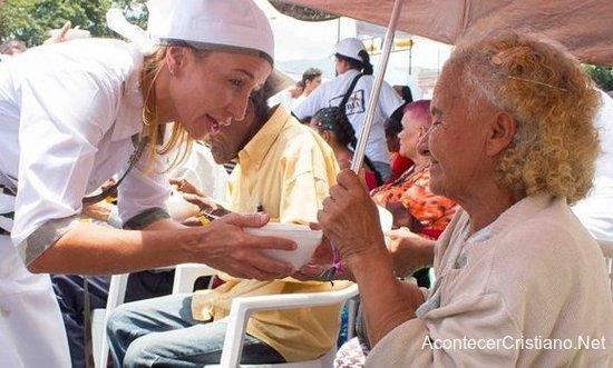 Mujer entregando comida a una anciana