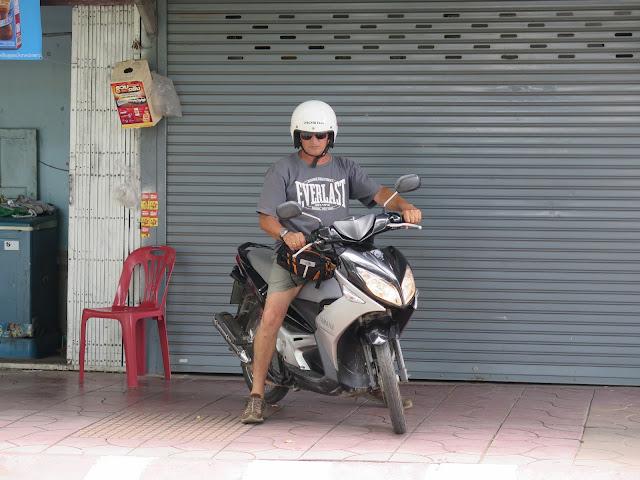 Yayo con su casco grande y su moto de alquiler