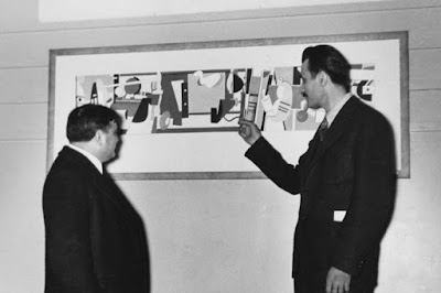 Image of two men evaluating an abstract work of art