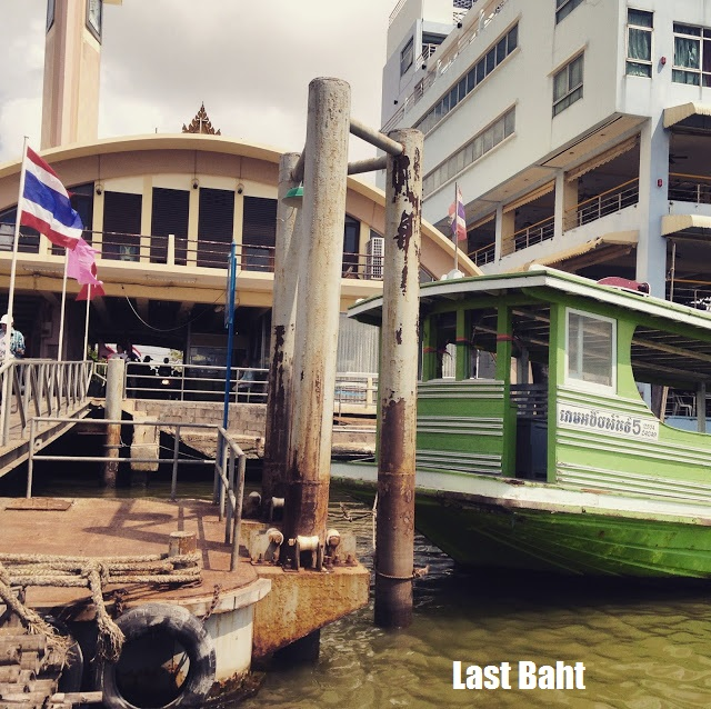 a green wooden ferry boat at a dock in Thailand