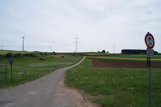 Eine weitläufige Landschaft, im Hintergrund sind einige Windräder zu sehen