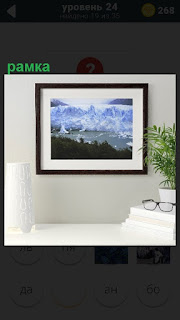 На стене висит картина в рамке, пейзаж, рядом очки и ваза с цветами