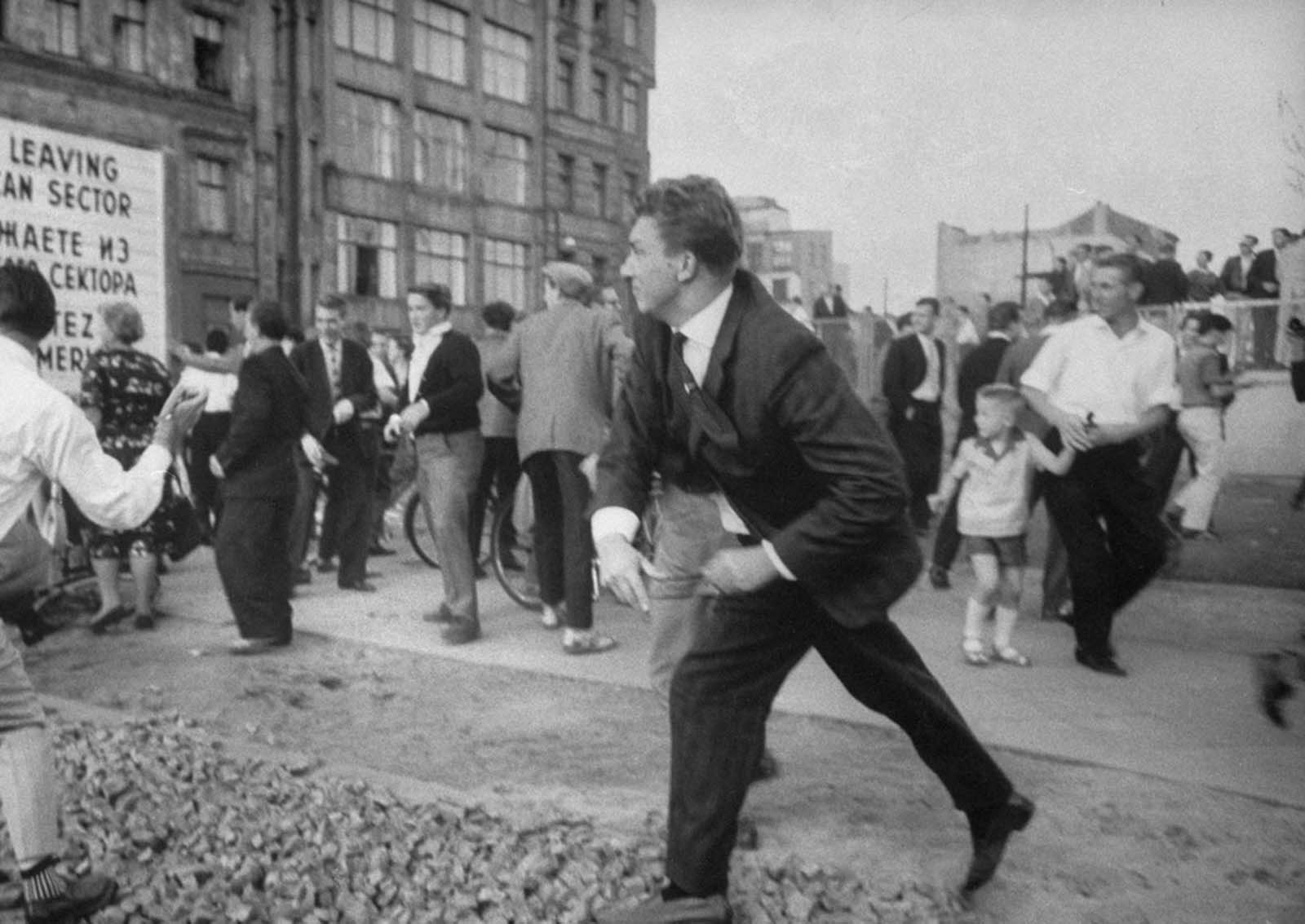 West Berliners, angered by taunts from East Berlin Police, throw rocks in August 1961.