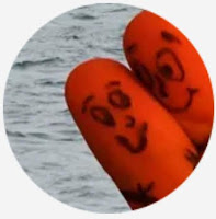 background of water with foreground of two crossed finger-tips with ink drawn faces, arms and hands to look like two-hugging smiley-faced things looking at one-another