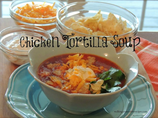 Chicken Tortilla Soup is best served with crushed tortilla chips, sour cream and cheddar cheese on top from Walking on Sunshine Recipes.