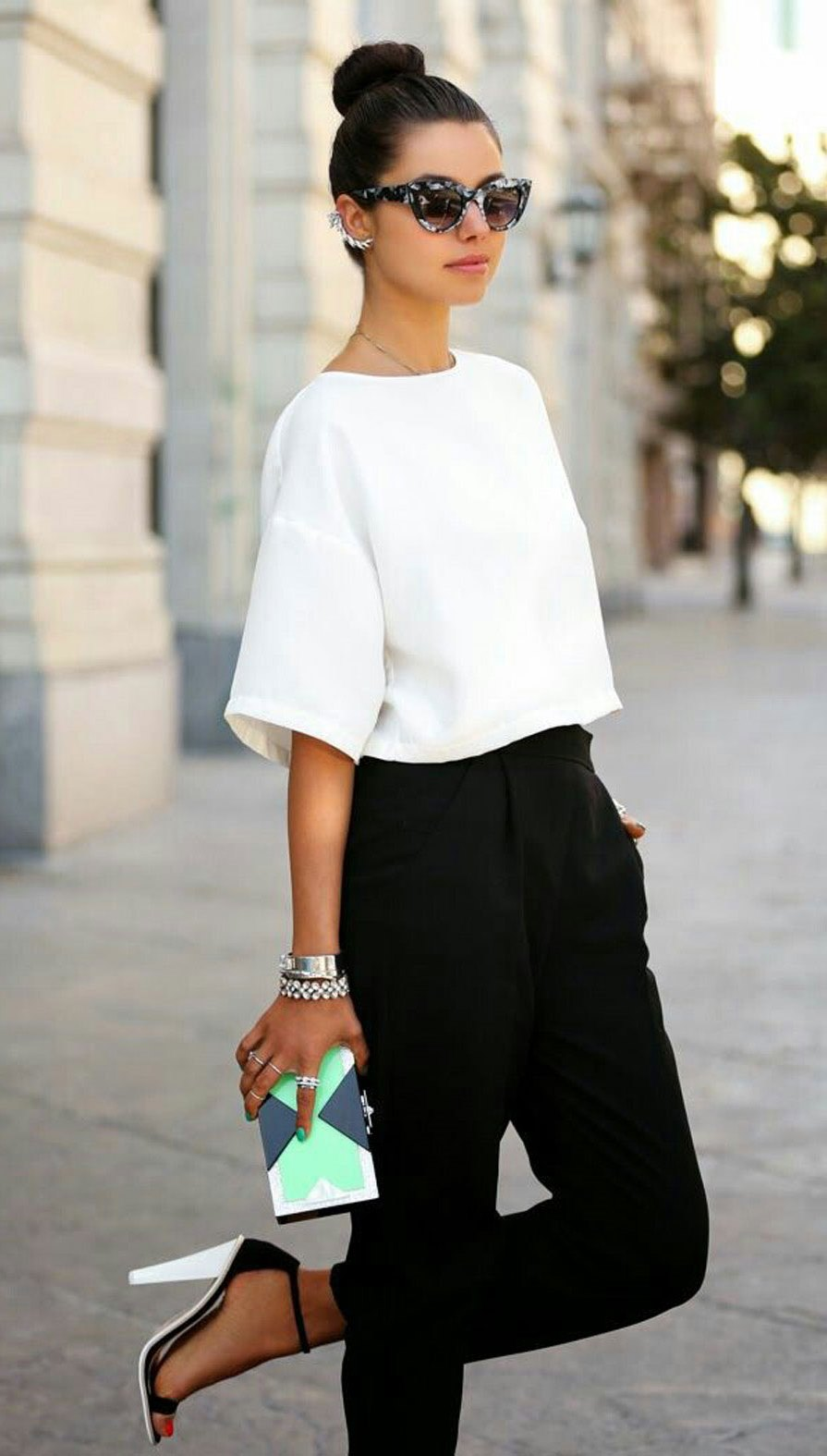 trendy outfit / white top + clutch + black pants + heels