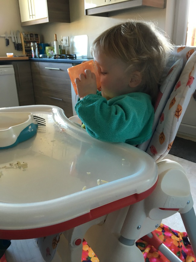 toddler in highchair with orange cup drinking water