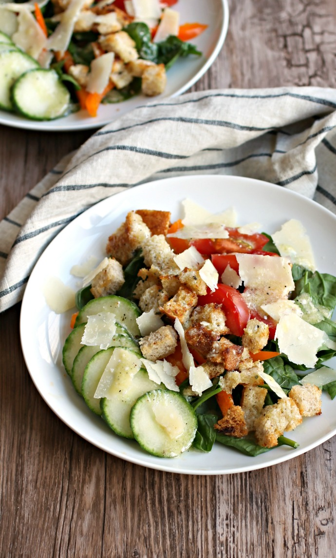 Recipe for a bread salad with tomatoes, cucumbers, bell peppers and Parmesan cheese croutons and dressing.