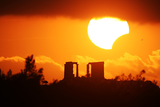 Eclipse over the Temple of Poseidon What's happened to the Sun? The Moon moved to partly block the Sun for a few minutes in January 2010 as a partial solar eclipse became momentarily visible across part of planet Earth. In this single exposure image, meticulous planning enabled careful photographers to capture the partially eclipsed Sun well posed just above the ancient ruins of the Temple of Poseidon in Sounio, Greece. Unexpectedly, clouds covered the top of the Sun, while a flying bird was caught in flight just to the right of the eclipse. At its fullest extent from some locations, the Moon was seen to cover the entire middle of the Sun, leaving the surrounding ring of fire of an annular solar eclipse.  Image Credit & Copyright: Chris Kotsiopoulos & Anthony Ayiomamitis Explanation from: http://apod.nasa.gov/apod/ap100118.html